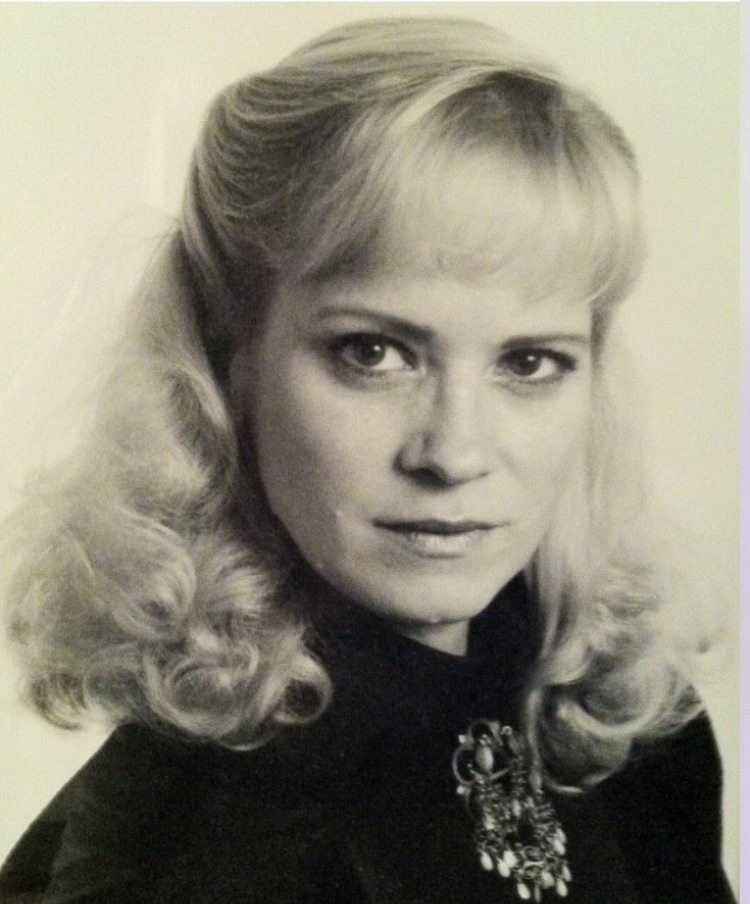Black and white portrait of Ingrid, a white woman with styled and curled blonde hair and bangs. She is wearing a black top with a jeweled broach.