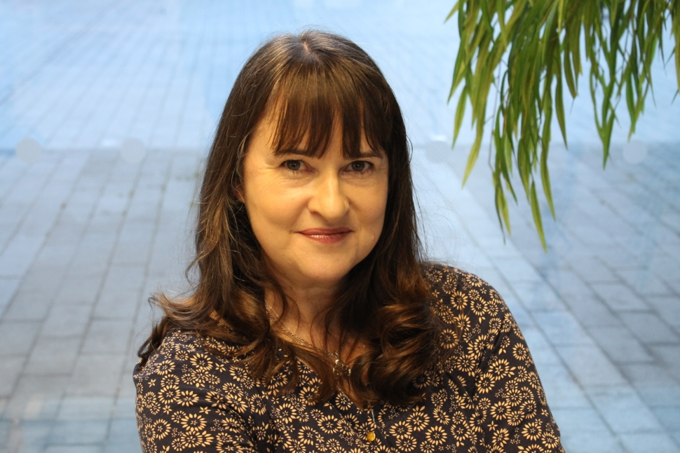 Image of Una, a white woman with brunette medium length hair and bangs. She is in front of a neutral background with leaves on the righthand side.