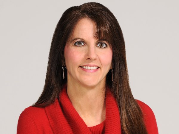 Picture of Lisa, a white woman with long Burnette hair, wearing a red sweater and silver earrings. She is in front of a neutral background.